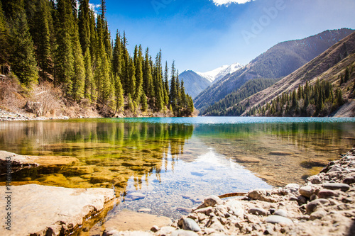 Majestic blue mountain lake with green trees Canvas Print