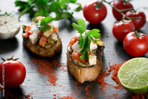 Tasty savory tomato Italian bruschetta, on slices of toasted baguette garnished with parsley