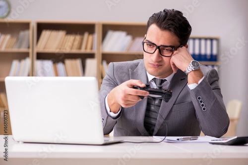 Businessman playing computer games at work office Poster