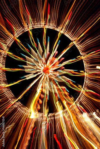 Lights from carnival rides are seen at a Christmas market in the