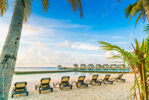 Poster Strand Beach chairs in Maldives island with water villas at the sunrise time .