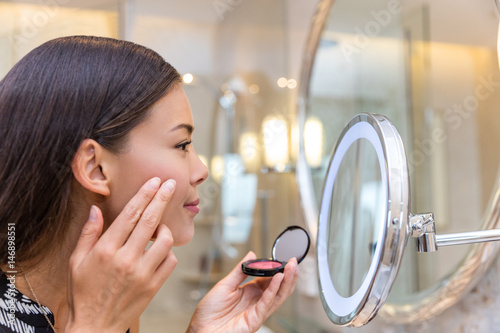 Asian young woman putting blush cream using fingers while looking in makeup mirror at home in bathroom Tablou Canvas