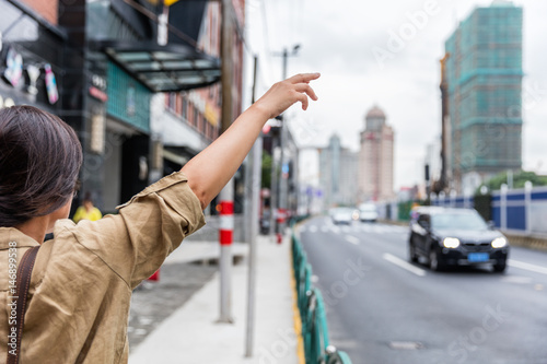 Photographie Hailing a rideshare black car on the road