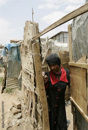 Girl stands at the door or her home in the slum area of Mahwa Dar