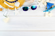 Summer Beach accessories (White sunglasses,starfish,straw hat,glass bottle,shell) on white plaster wood table top view,Summer vacation concept,Leave space for adding text