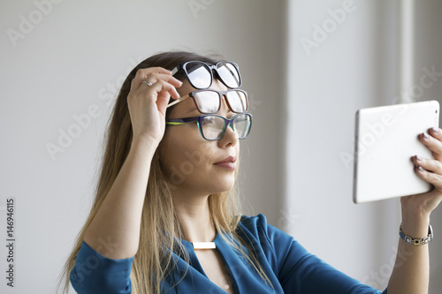 Ophthalmology metaphor - young pretty woman with three glasses on face watching Canvas Print
