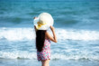 Backside Portrait of young Laos woman wearing hat and bikini enjoy on the tropical beach Rayong Thailand.
