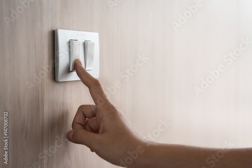 Papel de parede Close up hand turning on or off on grey light switch with wooden background