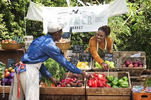 Greengrocer preparing organic fresh agricultural product at farmer market Fototapet