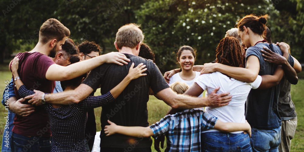 Fototapeta Group of people huddle together in the park