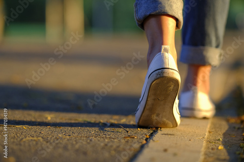 Foto  Sneaker and jeans walking on the road with beautiful sunset
