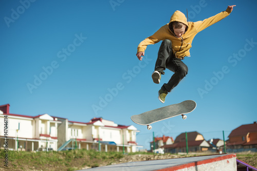 A teenager skateboarder does an flip trick in a skatepark on the outskirts of the city