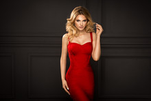Sensual Beautiful Blonde Woman Posing In Red Dress. Girl With Long Curly Hair.