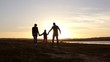 Silhouette, happy child with mother and father, family at sunset, summertime. Run, raising baby up in the air, hugs, love, playing. We are happy family.