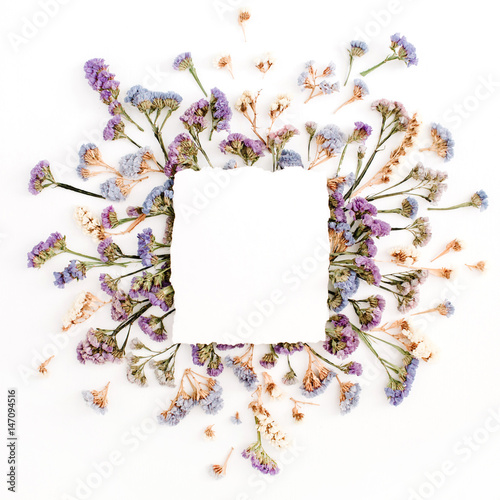 Stickers pour porte Pierre, Sable Empty white paper blank on blue and purple dried flowers frame on white background. Flat lay, top view