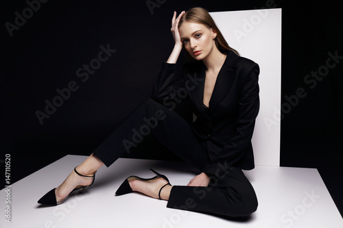 Foto  High fashion portrait of young elegant woman in black suit.
