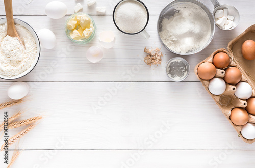 Photo Baking ingredients on white rustic wood background, copy space