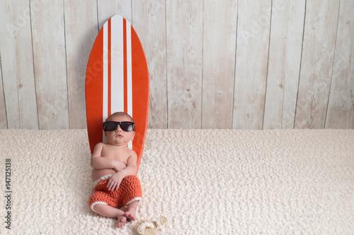 Photo  Newborn Baby Boy Leaning on Surfboard