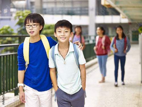 Photo  asian elementary school student walking on campus