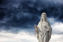 A Statue Of The Virgin Mary Against A Dramatic Sky.
