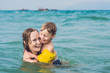 Young mother swimming and playing with male child boy in sea or ocean water sunny day outdoor on natural background, horizontal picture