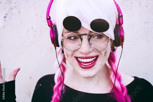Fotografie, Obraz  Adolescente con el pelo teñido y piercings escuchando música con unos cascos