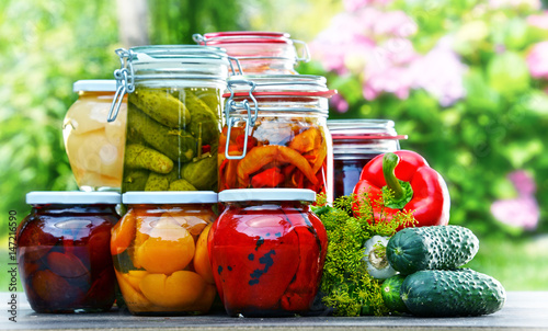Photo Jars of pickled vegetables and fruits in the garden