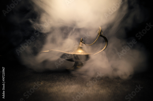 Carta da parati  Antique Aladdin arabian nights genie style oil lamp with soft light white smoke, Dark background