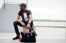 Portrait Of Sitting Stylish African American Man Wear On Sunglasses And Cap Outdoor. Street Fashion Black Man.