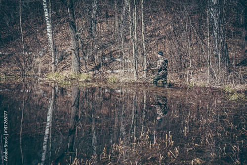 Foto op Aluminium Jacht Hunting scene with hunter man stealing in wetland with forest during hunting season