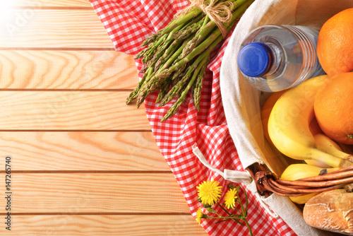 Plakat Pykniczny łozinowy kosz z jedzeniem na drewnianym stołowym wierzchołku