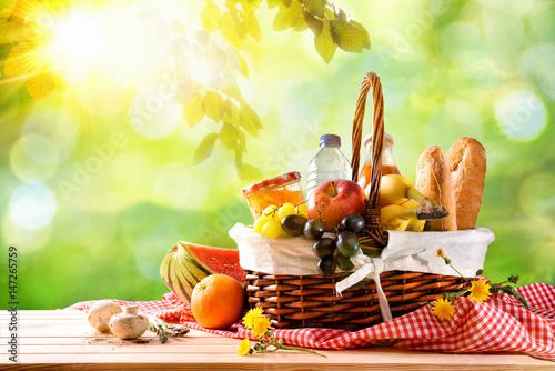 Plakat Pykniczny łozinowy kosz z jedzeniem na stole w polu