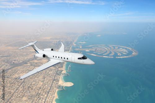 Fotografia Business jet airplane flying over Dubai city and sea coastline.