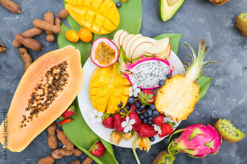 Exotic fruits. Summer photo concept. Mango. A pineapple. Avocado. Kiwi. Pitahaya.. Kumhvat. Copyspase. Fresh fruits. Exotic fruits on a gray background. Blueberry. Strawberry. Physalis. Tamarind