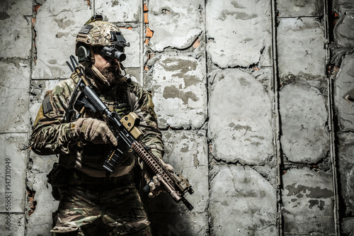 Fotografía  Army Ranger moving along the concrete wall on mission