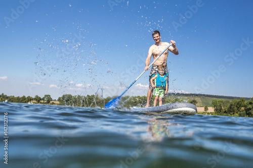 Fotografie, Obraz  Vater und Sohn haben Spaß beim Standup-paddling auf dem See