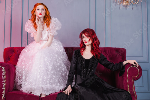Photo Two girls with red hair in retro dress in the bedroom