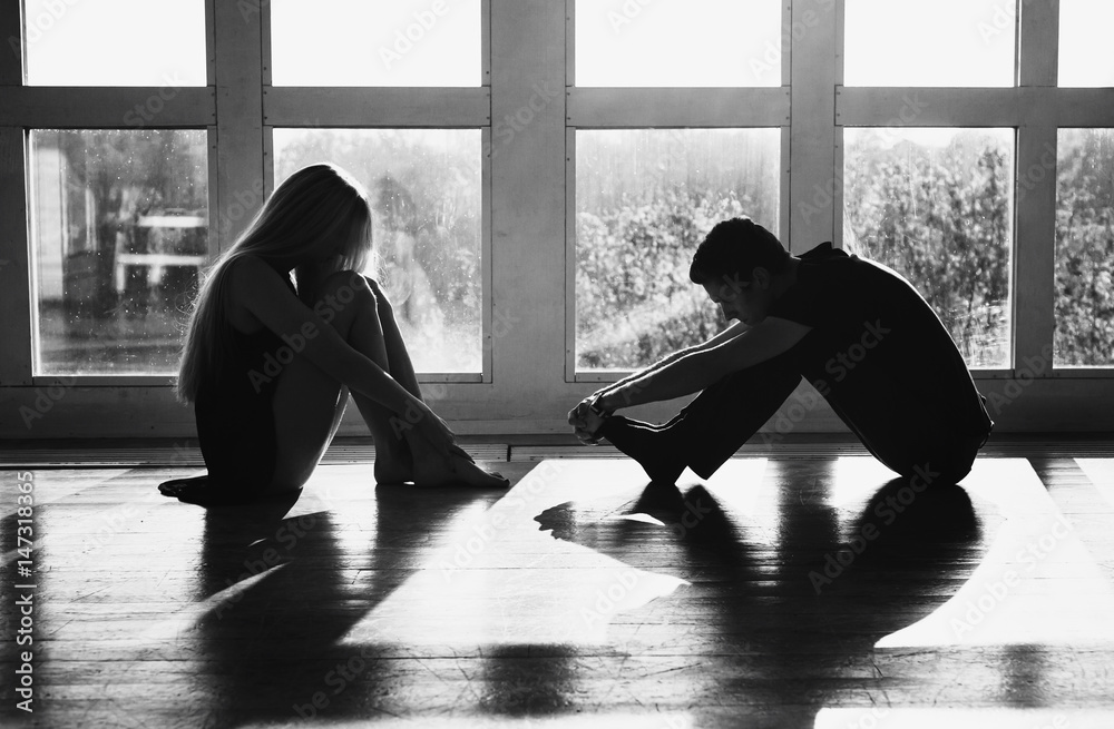 Fototapeta A young boy and girl with long blond hair standing in front of the window. Dancers during a workout. Problems and difficulties in relations. The difficult situation in life. Conceptual photography