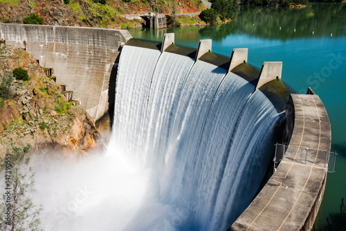 Tuinposter Dam Water spills over the top of Englebright Dam on the Yuba River. A larger than normal snowpack in the Sierra Nevada Mountains has increased runoff into lakes and rivers in California.