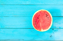 The Summer Watermelon Is Slice Of Half On A Blue Rustic Wood Background. Copy Space For Designer