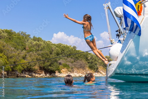 Foto op Aluminium Oceanië Children jumping from the sailboat