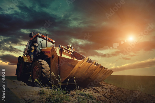 Leinwand Poster  Yellow tractor on sky background