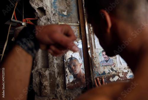 Palestinian man Mohammed al-Hoor, 23, is reflected in a