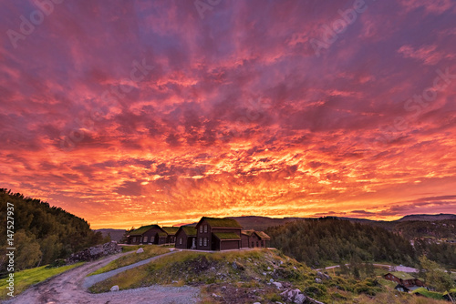 Poster de jardin Grenat Burning Sky in Norway. Local Village Architecture and Red Sky.