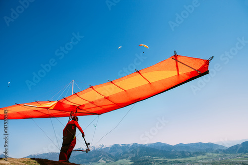 Canvas Prints Sky sports Man with hang-glider start to fly on the top of hill