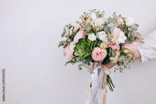 Foto op Canvas Bloemen Beautiful bouquet in the hands of a florist