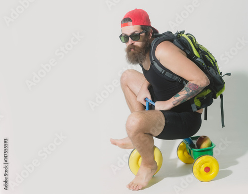 In de dag Indiërs bearded serious man with bag, apple on bicycle toy