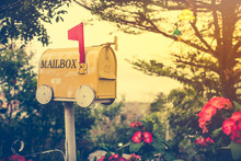 Old Yellow Stained Metal Mailbox Has Red Flag Raised Up To Indicate Mail Has Arrived. Outdoor On Summer Day With Bright Sunlight At Sunset. Vintage Effect Tone.