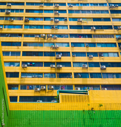 Photo  The wall of yellow  building with windows and air conditioners, can be used as b