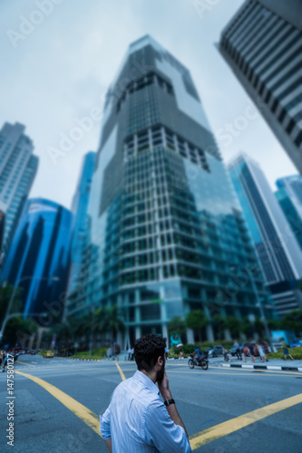 Photo Back view of man standing on the street against modern skycrapers and sky backgr